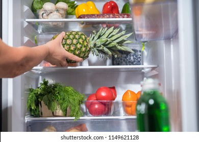 Person putting fresh pineapple into refrigerator full of food