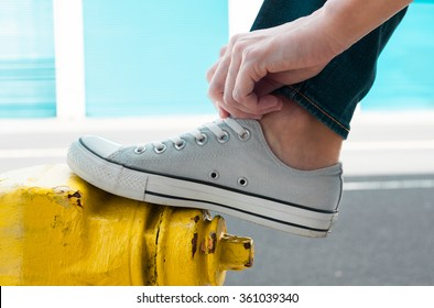 Person putting on pair of shoes. (Fashion concept)