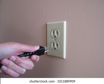 Person putting plug into American wall outlet