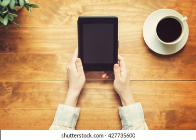 Person reading a book with an e-reader on a wooden desk