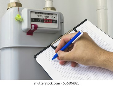 Person reading the gas meter in the private house, counter for distribution domestic gas. Cropped image, selective focus.