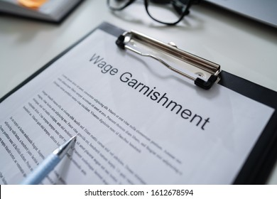 Person Reading  Wage Garnishment Documents At Desk