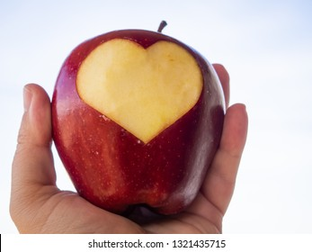 A person with a red apple in his hands with a cut in the shape of a heart. Health concept