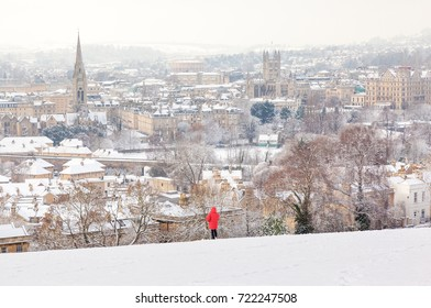 Person in a red jacket looking at the City of Bath from a snow covered hill.