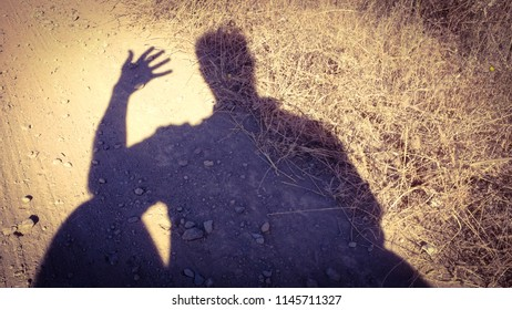 Person reflecting and thinking, stopped on the road. shadow on the road.