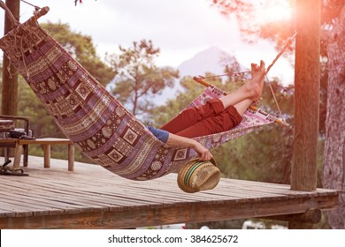 Person relaxing lying in Hammock at rural cottage garden female legs green flora and wooden hut on background