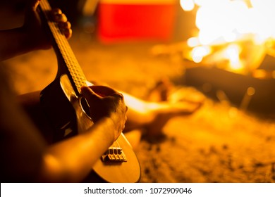 A person relaxing while sitting next to a campfire on a beach, playing a guitar