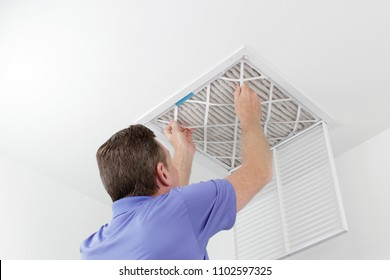 Person Removing Ceiling Air Filter. Caucasian male removing a square pleated dirty air filter with both hands from a ceiling duct. Guy taking out an unclean air filter from a home ceiling air vent