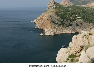 A person rests on cliff at seashore of the Crimean Peninsula