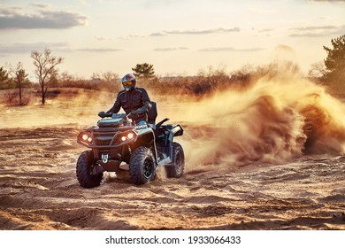 Person riding ATV in sand dunes making a turn in the sand