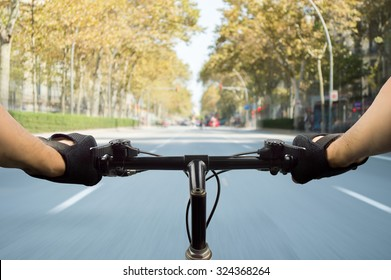 person riding a bicycle along a road in Barcelona Spain