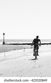 Person riding a bicycle on the beach on hard packed sand next to the water. Viewed from behind. Black and white. High key image. Copy space.