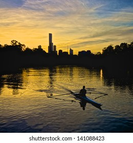 Person rowing on the Yarra river with the Melbourne city skyline in the background