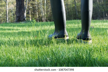 person in rubber work boots walking in grass