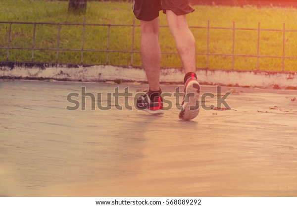 A person running outdoors on a sunny day, motion blur