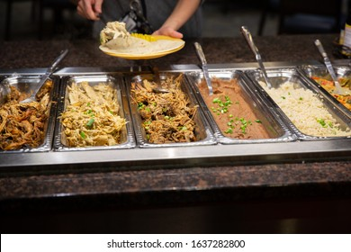 Person scooping food at a taco buffet line