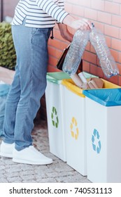 Person segregating plastic bottles into blue rubbish bin next to yellow and green bin against red brick wall