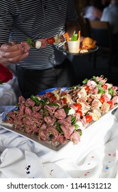 A person selecting an appetizer kabob with salami tomato and cheese from a white tray at a party.
