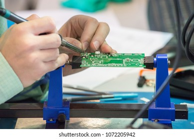 A person selects and solder the parts of the chip with a soldering iron with tin