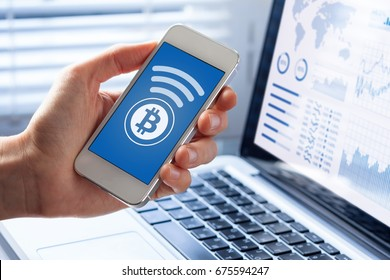 Person sending bitcoin with smartphone for online payment, closeup of mobile phone screen, business office background