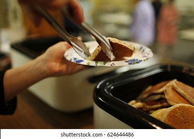 Person Serving Pancakes with Tongs on a Paper Plate