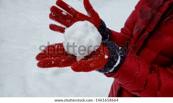 Person showing snowball to camera, winter entertainment, playing active games