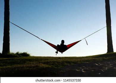 Person in silhouette sits in a hammock between two trees