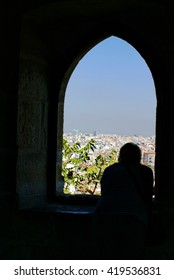 Person in silhouetted in a window in Sao Jorge Castle, with the city of Lisbon, Portugal below