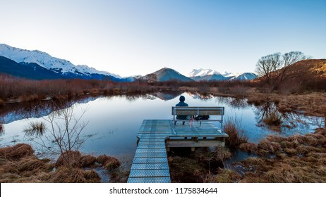 A person sitting alone on a bench in Glenorchy, New Zealand. The scenery is beautiful. This place is popular among tourists, backpackers and locals. The dawn sky is clear. The view is peaceful.