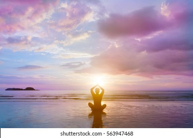Person is sitting in beautiful sunset sea beach, he is reflected in wet sand.Young man make meditation in lotus pose, yoga, zen and wellness concept.