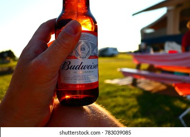 A person sitting at a campsite enjoying a Budweiser beer as the sun sets and the light highlights the bottle. Drinking Budweiser at the end of the day is relaxing.