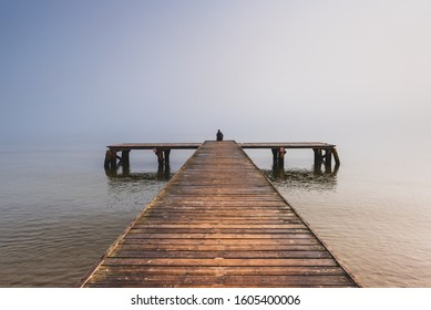 A person sitting at the end of the small pier and looking at the misty sea.