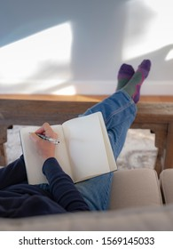 Person sitting on couch writing in blank journal