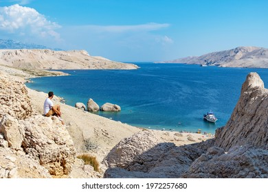 Person sitting on edge of cliff on rocky coastline near spectacular beach with rock formations in water on Beritnica beach on Pag island in Croatia