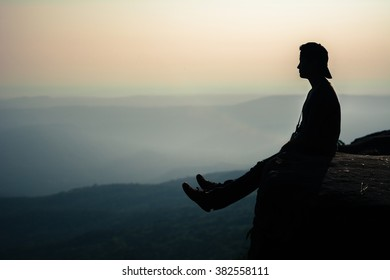 A person sitting on the edge of the cliff at Phu Ka Dueng national park in Loey, province of Thailand
