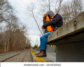 Person sitting on outdoor train platform with head resting on backpack