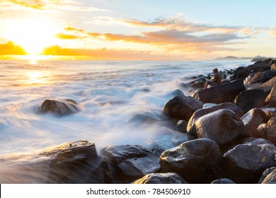 Person sitting on rocks at sunrise with ocean flowing over the rocks