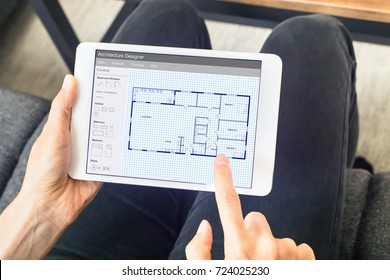 Person sketching a home design architecture project on a digital tablet computer app showing a blueprint floor plan drawing