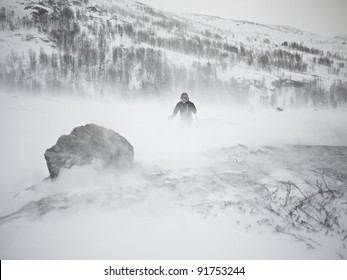 Person at ski in low visibility conditions due to a snow storm with a rock in the foreground in the norwegian mountains at winter time