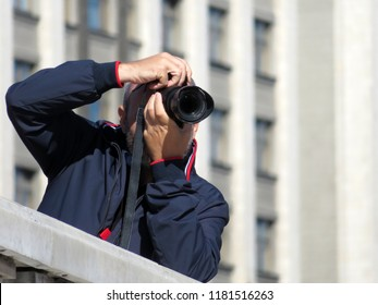 Person with a SLR camera in his hands. Man photographing in sunny day outdoor on city background, concept for paparazzi, photo reporter