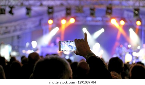 person with smartphone while taking photographs during a rock live concert