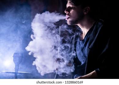 person smoke hookah in dark place