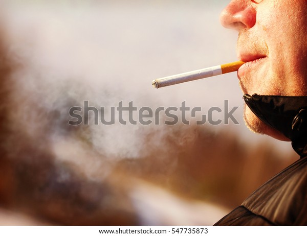 A person is smoking a cigarette outdoor on a cold morning. Caucasian man has just lighted the cigarette outdoors. Image has a vintage effect.