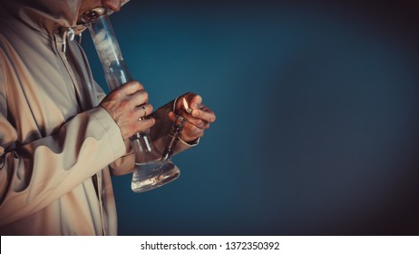 The person smoking marijuana with bong, close-up. Bong in the hand.