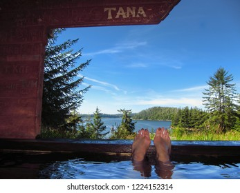 Person soaking in hot spring with ocean view
