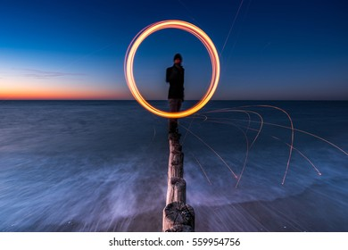 Person spinning fire on top of pole heads at the beach at dusk with long exposure