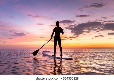 Person stand up paddle boarding at dusk on a flat warm quiet sea with beautiful sunset colors