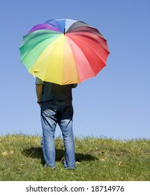 A person standing alone, watching the horizon, with a rainbow coloured umbrella.