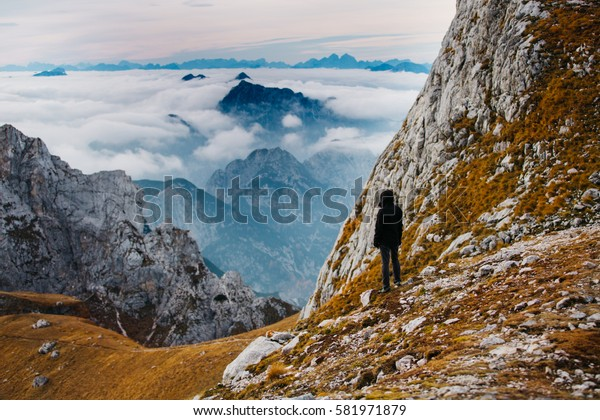 Person standing and enjoying the view from Mangart mountainst, located between Italy and Slovenia. In the background with foggy peaks of Triglav