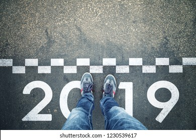 Person standing in front of a start New Year 2019 sign painted on asphalt city street. Point of view perspective used.